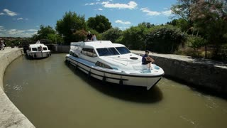 CANAL DU MIDI, FRANCE - JUNE 22: Boat exiting lock on June 22, 2013 on the Canal du Midi, France. The UNESCO listed canal was built in 17th century stretching from Toulouse to Bezier.