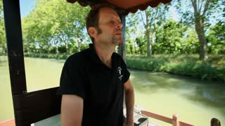 CANAL DU MIDI, FRANCE - JUNE 22: Captain driving tourists on barge on June 22, 2013 on the Canal du Midi, France. Tourism is the main activity and source of income on the canal du midi.