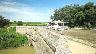 CANAL DU MIDI, FRANCE - JUNE 22: Passengers on boat in summer on June 22, 2013 on the Canal du Midi, France. The UNESCO listed canal was built in 17th century stretching from Toulouse to Bezier.