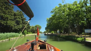 CANAL DU MIDI, FRANCE - JUNE 22: Travelling on a wooden boat on June 22, 2013 on the Canal du Midi, France. The UNESCO listed canal was built in 17th century stretching from Toulouse to Bezier.