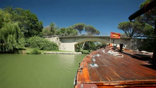 CANAL DU MIDI, FRANCE - JUNE 22: Travelling wooden boat under bridge on June 22, 2013 on the Canal du Midi, France. UNESCO listed canal was built in 17th century stretching from Toulouse to Bezier.
