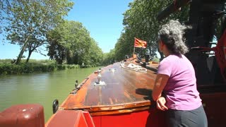 CANAL DU MIDI, FRANCE - JUNE 22: Woman on a wooden boat on June 22, 2013 on the Canal du Midi, France. The UNESCO listed canal was built in 17th century stretching from Toulouse to Bezier.