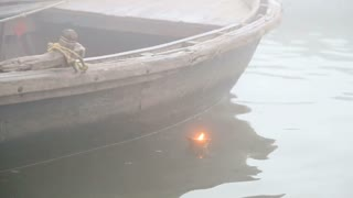 Candle burning on river Ganges by a boat anchored in bay.