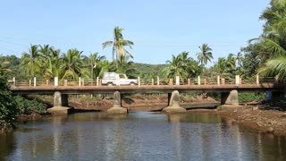 Cars passing the bridge above the river in Goa.
