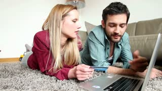 Charming blond girl holding credit card and lying on carpet with partner