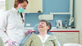 Cheerful elderly patient talking with dentist
