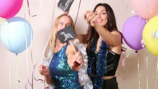 Cheerful friends dancing with a sign in love in party photo booth