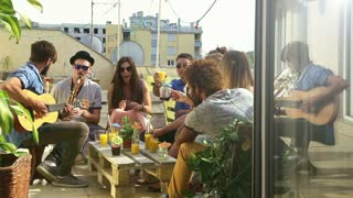 Cheerful friends toasting on a rooftop terrace