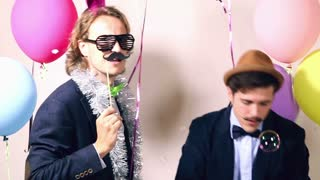 Cheerful male friends dancing in photo booth