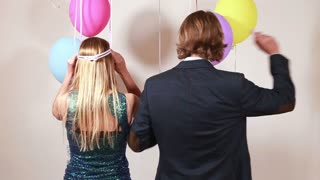 Cheerful woman and man dancing in photo booth