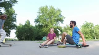 Cheerful young skateboarders chilling and doing tricks on skateboard