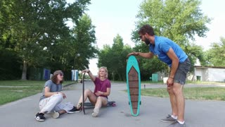 Cheerful young skateboarders chilling and playing with their skateboard
