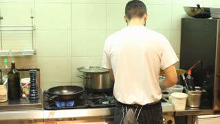 Chef cooking meat in kitchen of restaurant