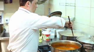 Chef cooking stirring pot in kitchen