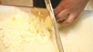 Chef slicing onions in kitchen
