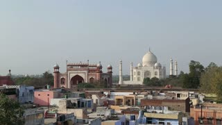 Cityscape view of Agra, with Taj Mahal in background.