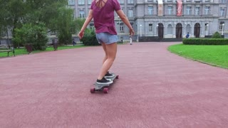 Close low angle view of women legs riding on a longboarding