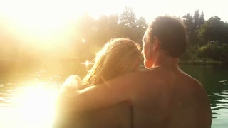 Close up back view of beautiful couple in love sitting by the Mreznica river at sunset, kissing and smiling, graded