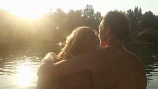 Close up back view of beautiful couple in love sitting by the Mreznica river at sunset, kissing and smiling