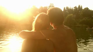 Close up back view of beautiful couple in love taking selfies and kissing while sitting by the Mreznica river at sunset, graded