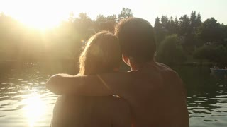 Close up back view of beautiful couple in love taking selfies and kissing while sitting by the Mreznica river at sunset