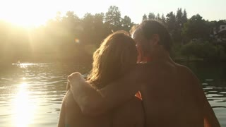 Close up back view of beautiful couple in love taking selfies and laughing while sitting by the Mreznica river at sunset