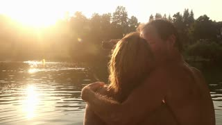 Close up back view of beautiful couple in love taking selfies while sitting by the Mreznica river at sunset, graded
