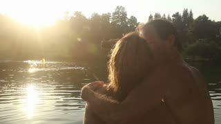 Close up back view of beautiful couple in love taking selfies while sitting by the Mreznica river at sunset