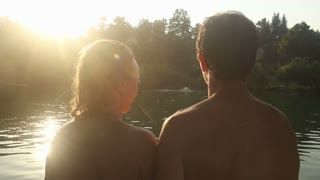 Close up back view of beautiful happy couple looking at river while sitting next to the Mreznica river at sunset