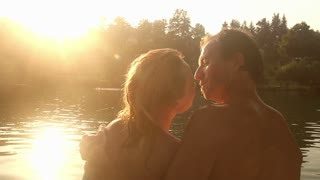 Close up back view of beautiful romantic couple kissing and hugging while sitting by the Mreznica river at sunset, graded