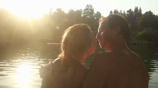 Close up back view of beautiful romantic couple kissing and hugging while sitting by the Mreznica river at sunset