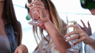 Close up low angle shot of woman dancing with friends with glass of champagne