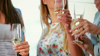 Close up mid-section of three woman holding glasses with champagne