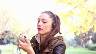 Close-up of a beautiful young woman listening to music on headphones and dancing, graded