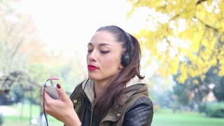 Close-up of a beautiful young woman listening to music on headphones and dancing