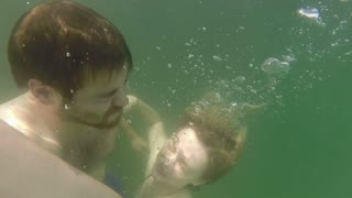 Close up of a cute young couple underwater, in slow motion