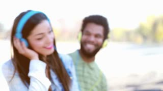 Close up of a young couple with headphones listening to music and dancing to the rhythm at the park, slow motion, graded