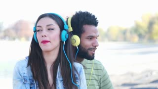 Close up of a young couple with headphones listening to music and dancing to the rhythm at the park