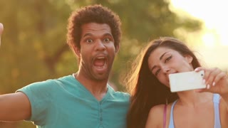 Close up of a young multi-ethnic couple having fun goofing around and making funny faces while taking a  selfie at sunset.
