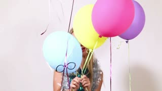 Close up of attractive blonde woman playing with balloons in photo booth