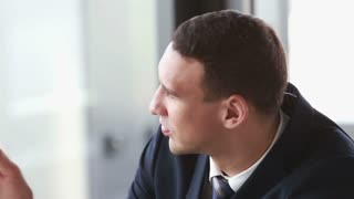 Close up of attractive young businessman writing in notebook during a meeting