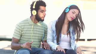 Close up of attractive young couple having fun listening to music with headphones on nice sunny day, graded