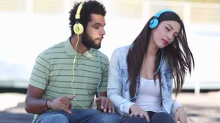 Close up of attractive young couple having fun listening to music with headphones on nice sunny day