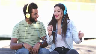 Close up of attractive young couple listening to music with headphones and dancing on nice sunny day, graded