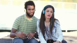 Close up of attractive young couple listening to music with headphones on nice sunny day, graded