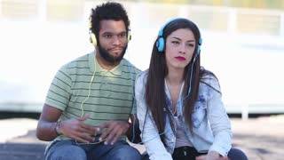 Close up of attractive young couple listening to music with headphones on nice sunny day