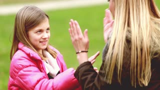 Close up of attractive young mom and her cute daughter playing clapping game, graded