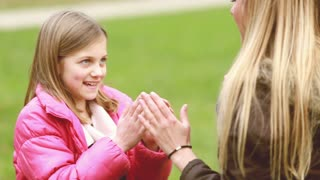 Close up of attractive young mom and her cute daughter playing clapping game, slow motion, graded
