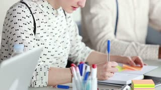 Close up of attractive young woman writing in notebook during business meeting, male colleague in background