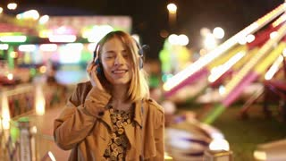 Close up of beautiful blonde girl dancing to the rhythm of music with headphones in amusement park